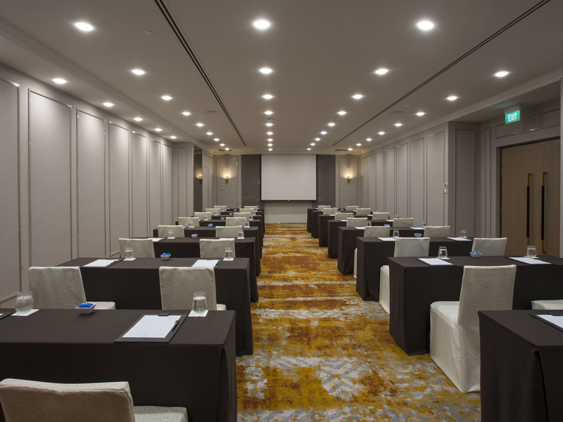 seminar room for corporate event with high ceiling and screen projector