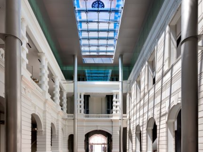 neoclassical hallway building with large glass roof