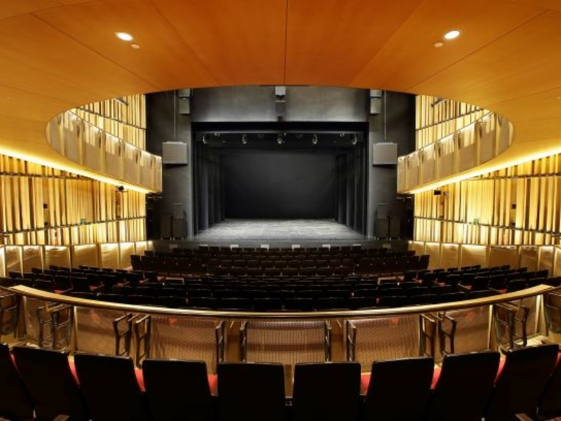 concert hall with a proscenium black stage and yellow cove light