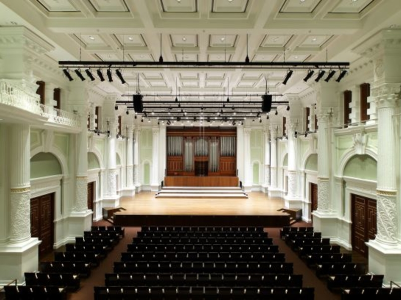 neoclassical white theatre hall with black audience chairs