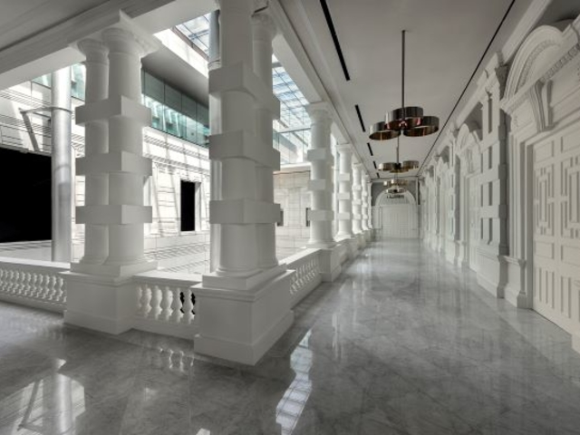 white neoclassical building with high pillars and silver pendant lamps