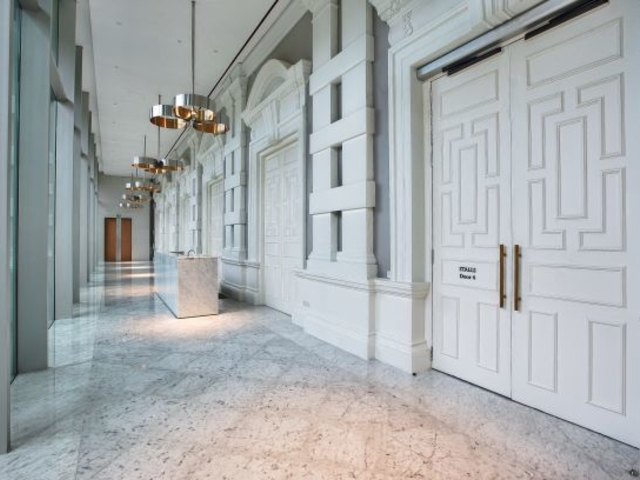 white hallway building that has marble floor and silver pendant lights