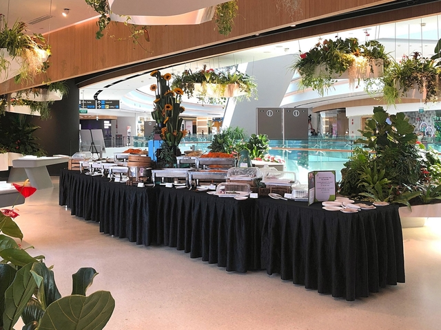 food set up table for standing party beside indoor pool