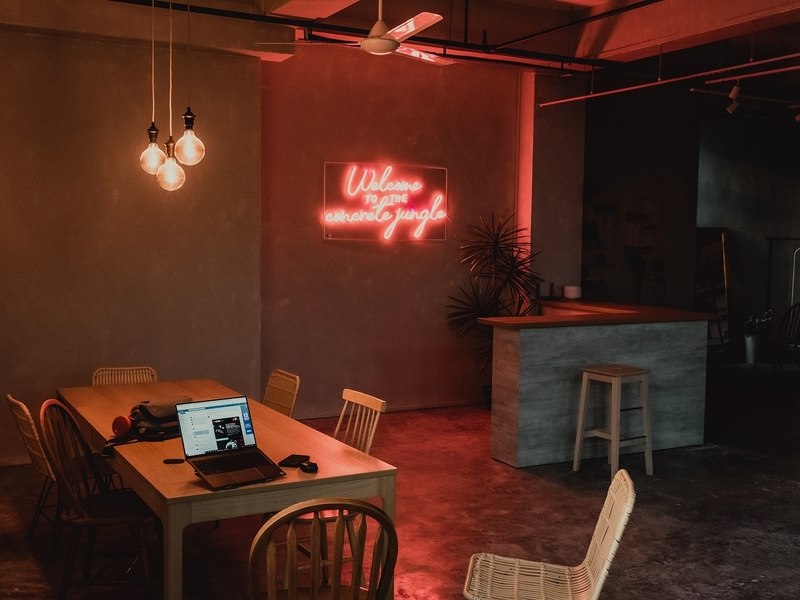 romantic venue setup with hanging dim light and pink neon sign on the wall