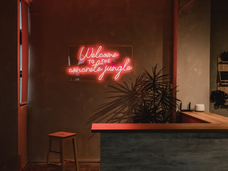 neon sign says welcome to the concrete jungle