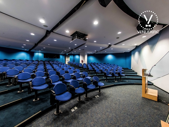 small auditorium equipped with a blue audience chairs and a podium speech table