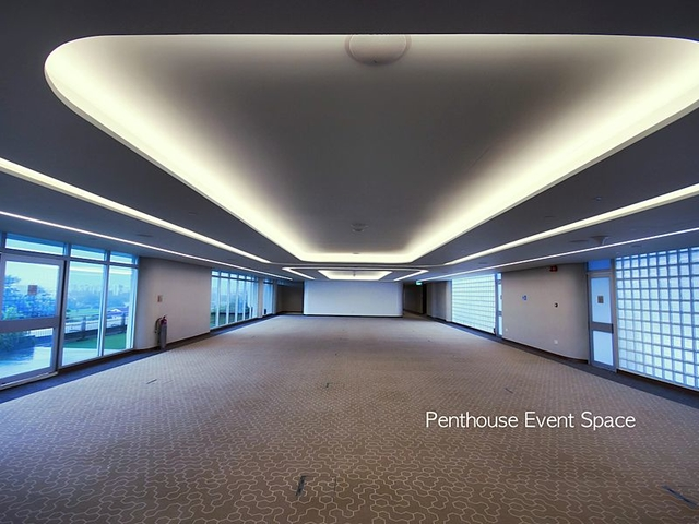 large function room with dropped ceiling light and several fixed windows