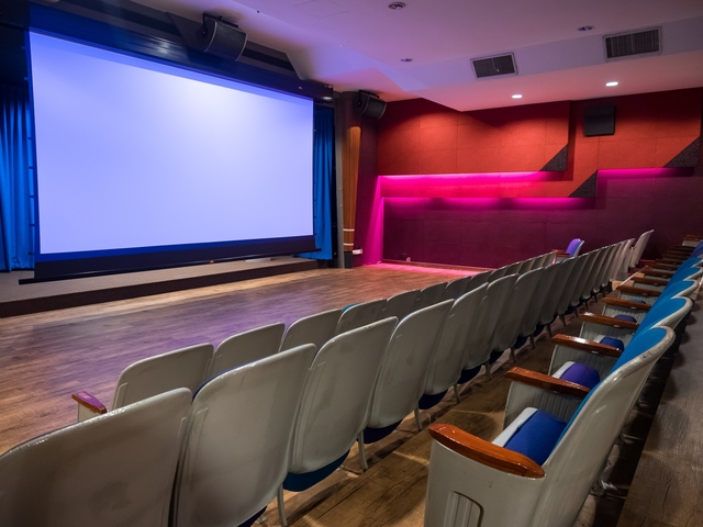 a private theatre with a spacious front and grey audience chairs