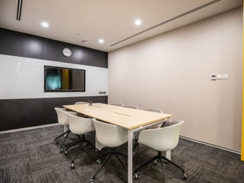 small conference room with television and several mid-back office chairs
