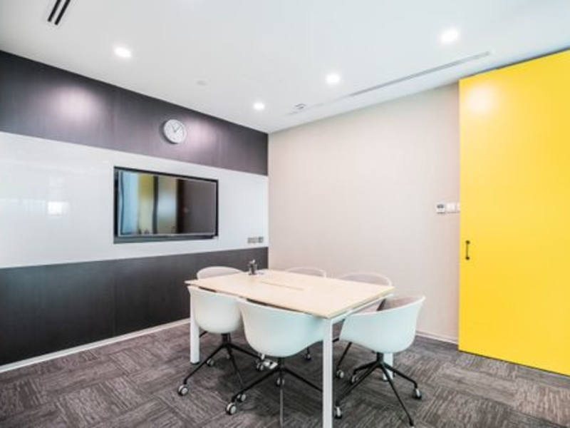mini-conference room with yellow door in a coworking space