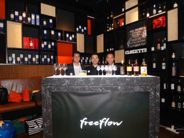 three men standing in a room full of whiskey displays