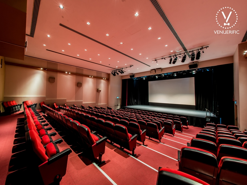red theme auditorium with stage and screen projector
