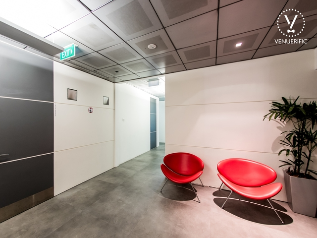 waiting room in the corner with two red chairs