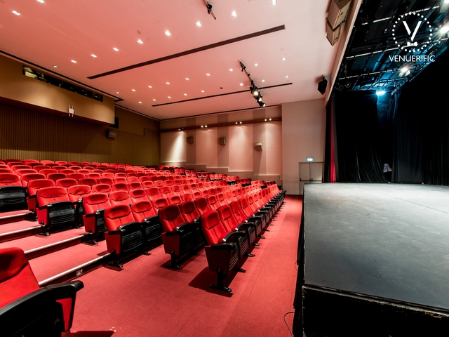 side corner of the auditorium with red chairs and carpets