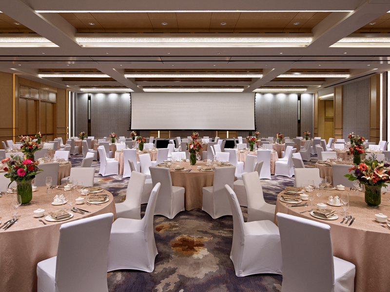 round dining table and large projector screen in singapore hotel ballroom