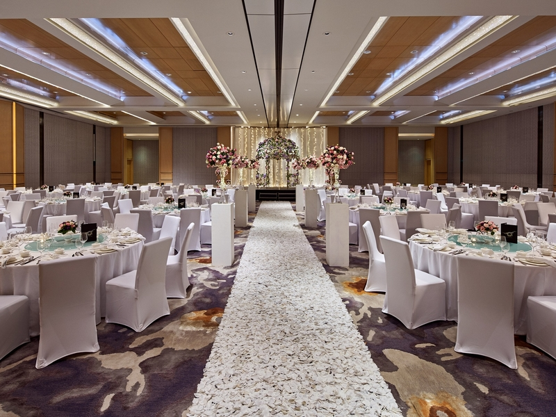 ballroom decorated with flowers on wedding aisle and several round dining tables