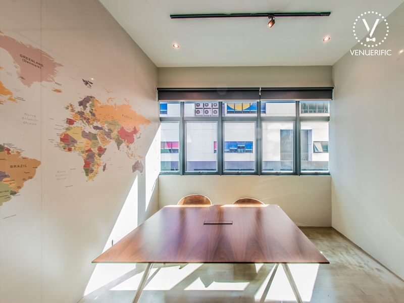 small meeting room equipped with a brown square table and world's map on the wall