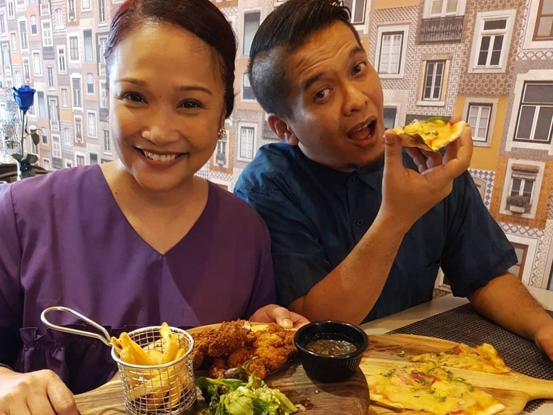 man and woman take photos with one of the signature dish from grll ninety nine