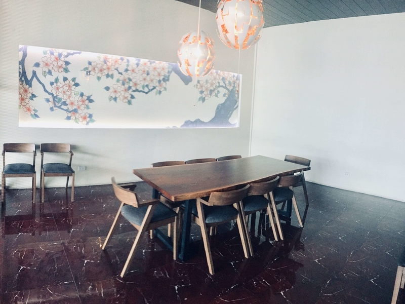 private dining room with long wooden table and painting decorations in makati restaurant