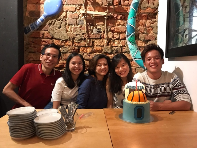 family celebrate a birthday party together with basketball cake