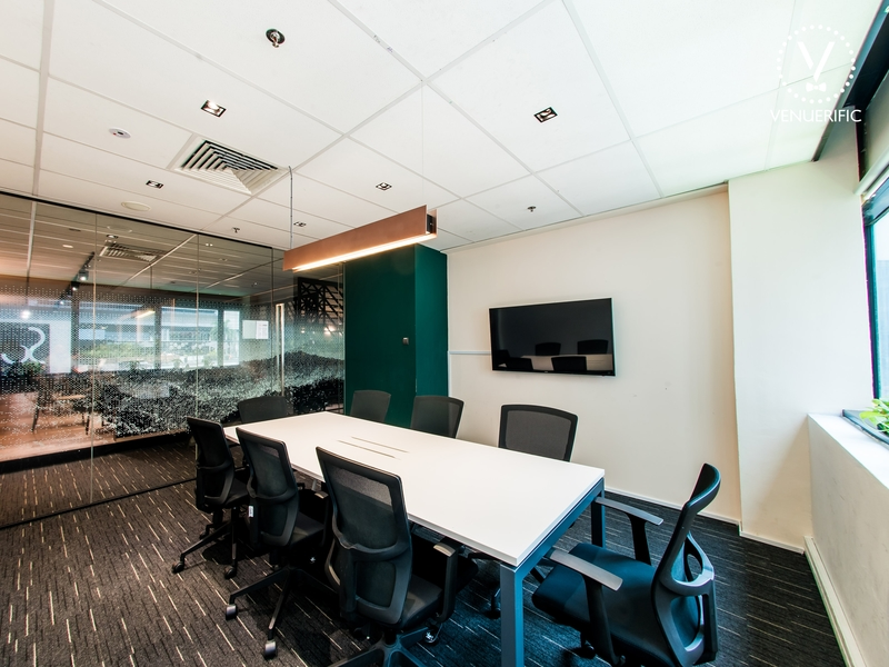small meeting room setting with tv screen and table chairs