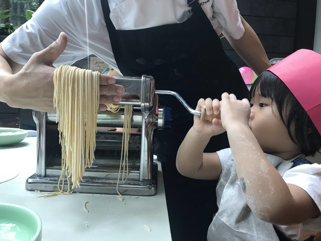 a child in a pink hat is making pasta