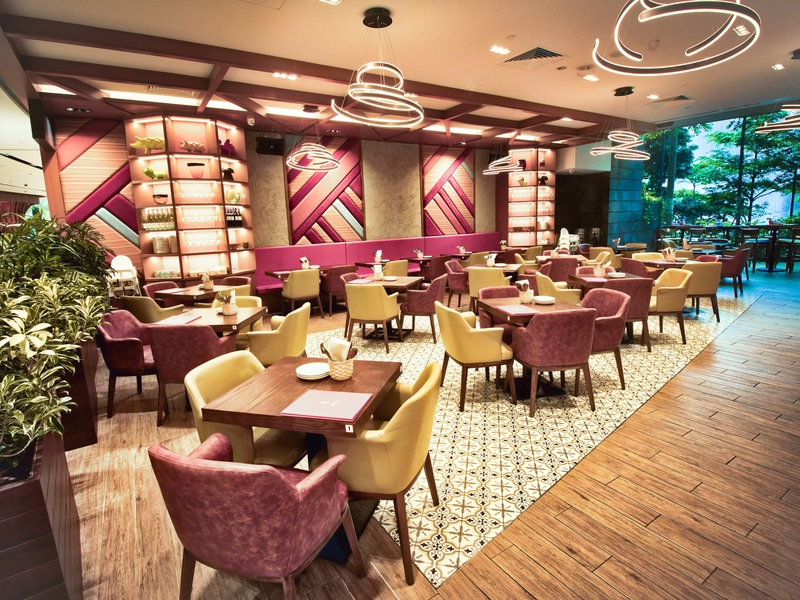 large restaurant with wooden floors and pink patterned walls