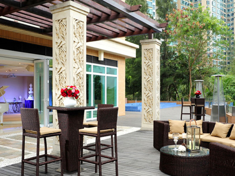 the outdoor area near the pool with high table and chair