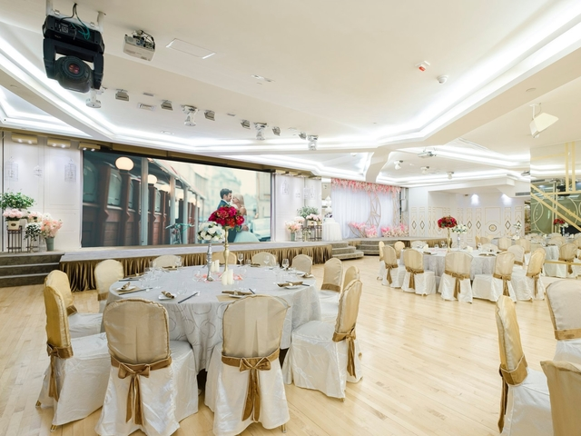 round table setup inside the grand ballroom with couple photo as the backdrop