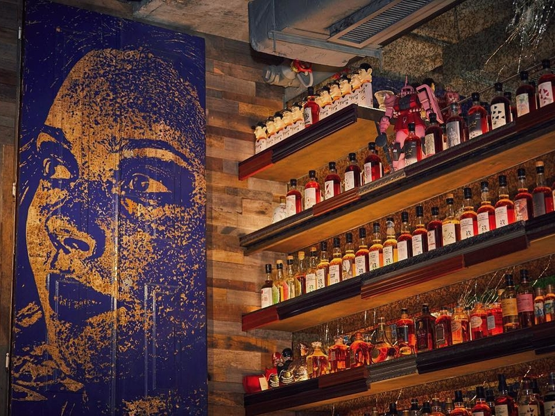 the bar area of djapa with the selection of alcohol drinks and woman painting on the wall