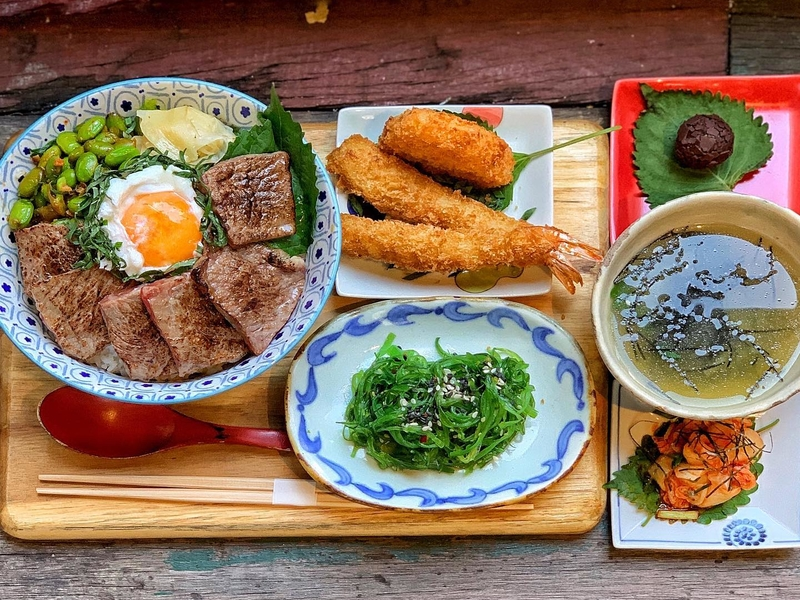 lunch set with main course options of salmon, beef accompanied by shrimp, a refreshing seaweed salad, miso soup, kimchi