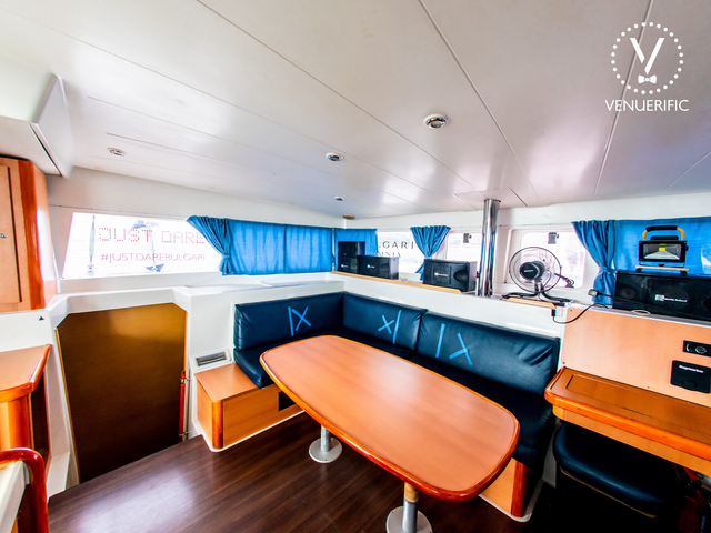 singapore yacht main deck with long black couch and wooden interior