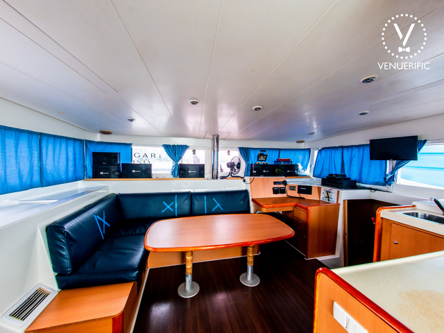 low ceiling yacht deck with long black couch and blue curtain