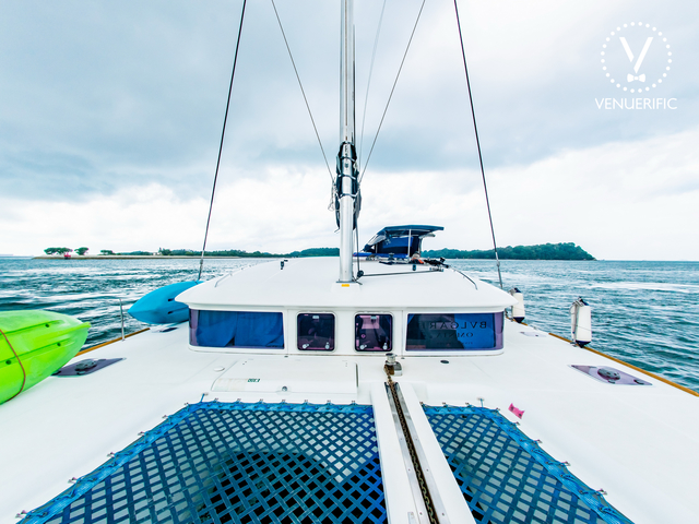 large singapore yacht with blue net and canoe