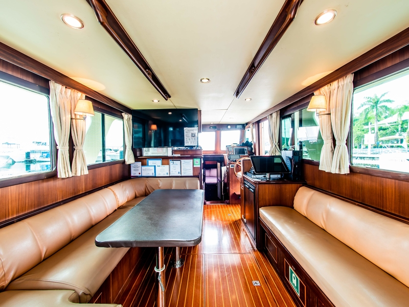 main deck with brown interior and long couches in singapore yacht
