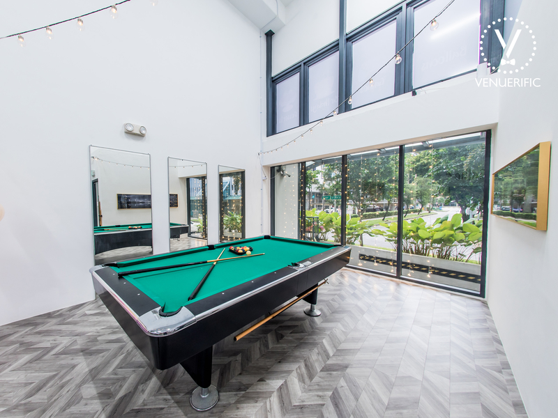 high ceiling white venue in singapore with pool table and large windows