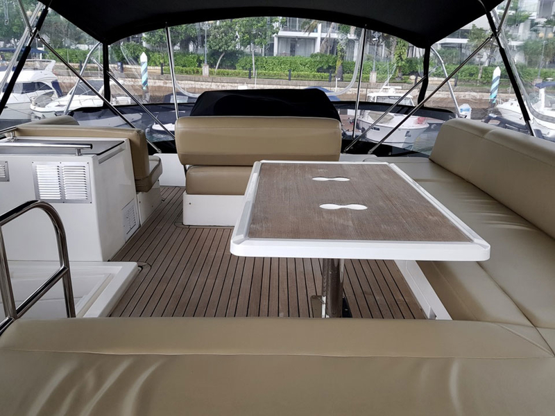 upper deck boat in singapore with long beige couches and table