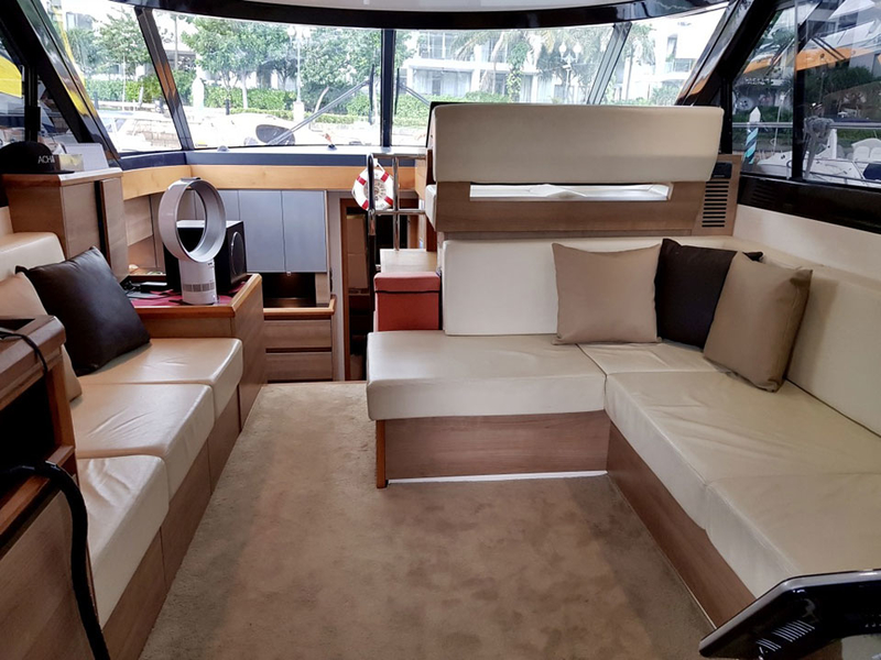 beige long couches and large windows in singapore party boat