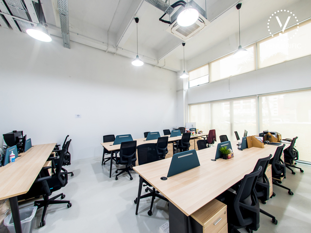 long tables and high ceiling in singapore coworking space
