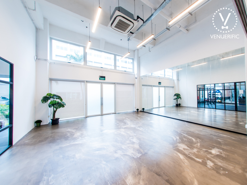 high ceiling event room in singapore with white interior and big mirror