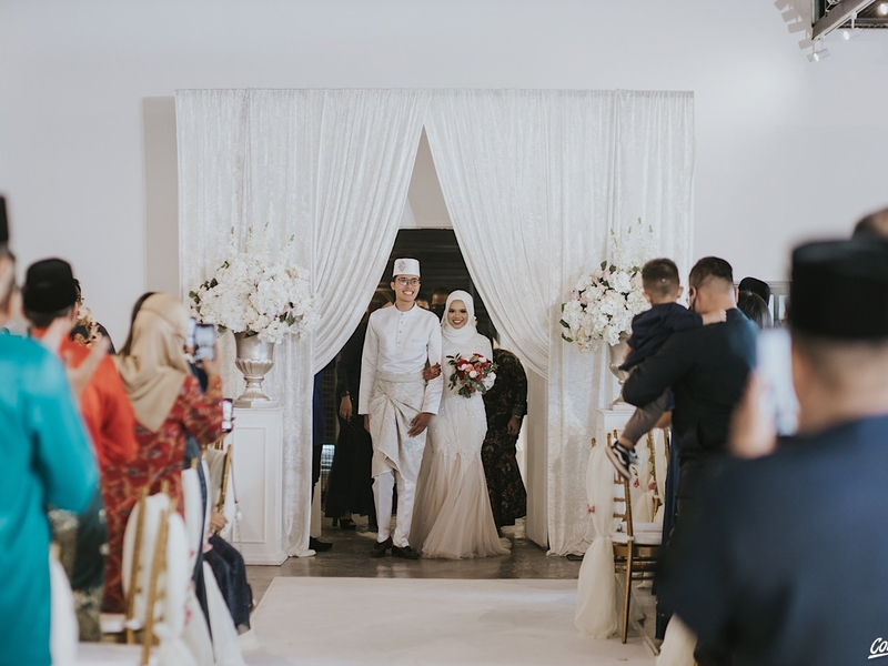 malay bride and groom in singapore wedding venue with white interior