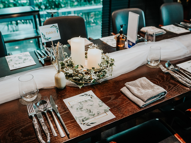 wooden dining table decorated with white candle and wedding flowers