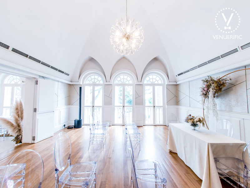 arch ceiling wedding venue in singapore with white interior and transparent chairs