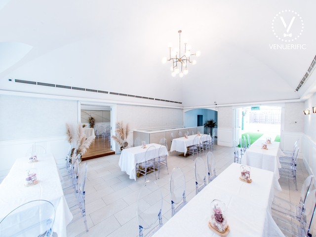 white theme wedding venue in singapore with several long tables and transparent chair