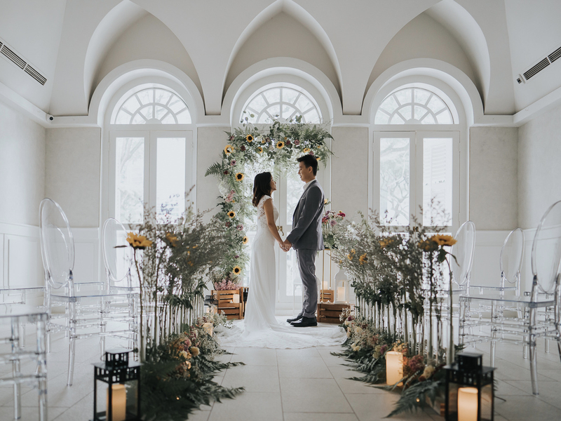 groom and bride standing in singapore white interior wedding venue with arch windows
