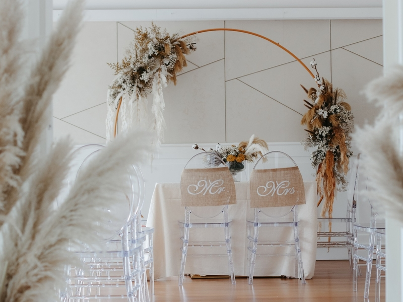 transparent groom and bride's chair with beige colour decorations in singapore wedding space