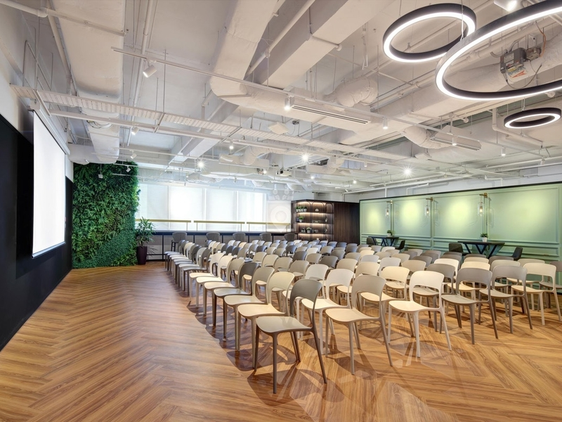 green walls event venue in singapore with projector screen and audience chairs