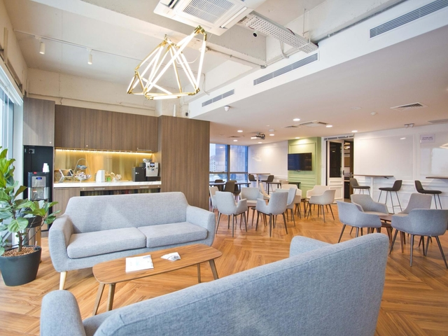 large space with wooden floors and several grey sofa in singapore business lunch space