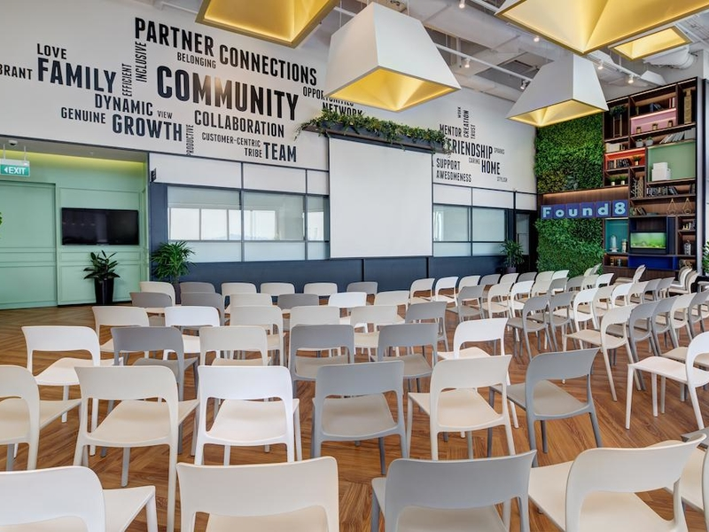 high ceiling workshop space in singapore with projector screen and audience chairs