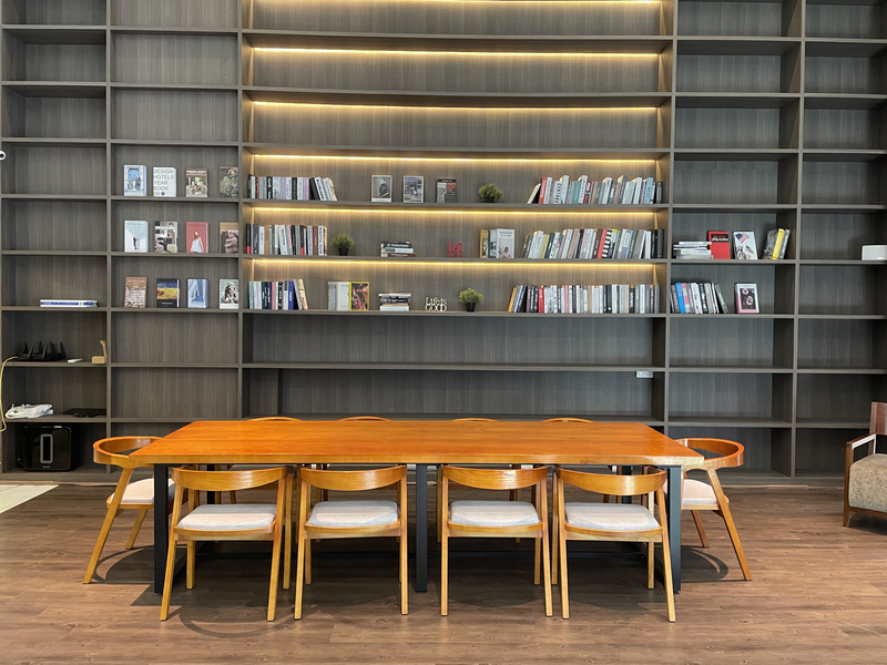 long wooden table and large bookshelf in singapore meeting venue